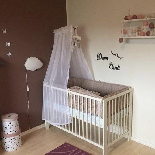 Baby trammeseng med tekst på væg