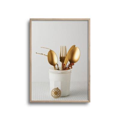 plakat af guld bestik i beholder på hvid baggrund